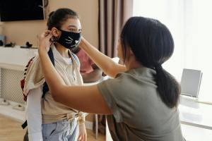 Mom fixing a mask on her daughter using the principles of applied behaviour analysis.