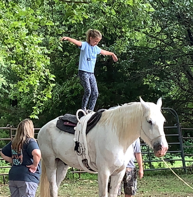 Daughter Avery standing on a horse at vaulting clinic.
