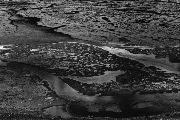 A geologic anomaly (a mudflat with scattered pools of water connected by a stream) in the Canadian Rockies during mid-spring runoff, black and white fine art Alberta landscape.
