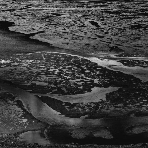 A black and white version of the geologic anomaly that is Medicine Lake, which is essentially a mudflat with scattered pools of water connected by a stream, captured here during mid-spring runoff. Jasper National Park, Alberta.