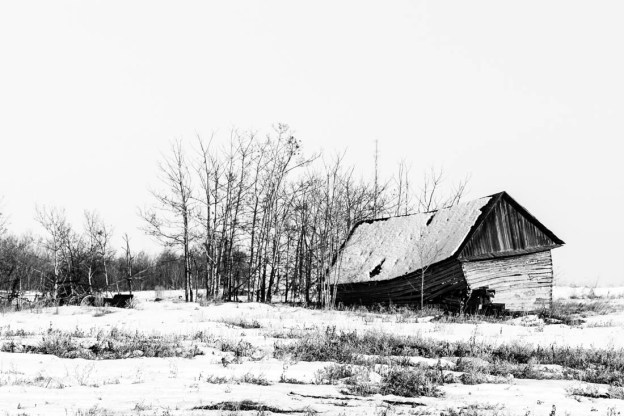 An abandoned old shack rests on the snow-covered farmland littered with pieces of equipment which were once in use, black and white Alberta deserted structures.