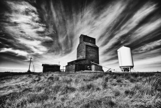 Black and white Killearn grain elevator in rural Alberta during an early autumn day.