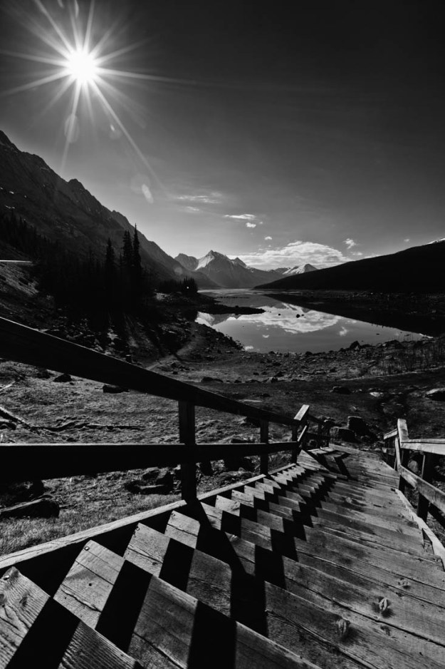 Black and white wooden stairs leading down to Medicine Lake in Jasper National Park, Alberta landscape.
