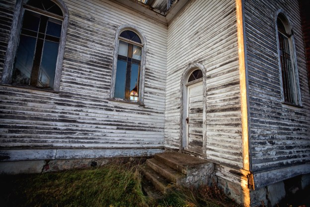 Autumn sunrise of the Spaca Moskalyk exterior showing the side stairs and remaining stained glass windows outside of Mundare, Alberta deserted structures.