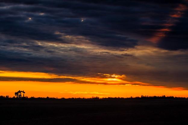 Two pumpjacks operating during a sunrise on the rural Alberta prairies, Alberta landscape, Alberta Oil and Gas.