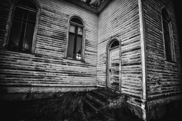 Spaca Moskalyk exterior showing the side stairs and remaining stained glass windows, black and white Alberta deserted structures.