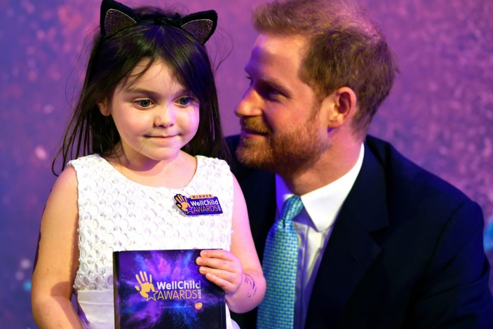 Prince Harry with a child at the Wellchild awards 2019