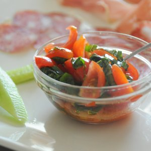 image of a glass ramekin with tomato and basil salad showing a slice of cucumber at the left and salami out of focus in the back ground