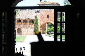 Image of the central square of a tuscan borgo showing the red brick and stone buildings, arches and loggia with geraniums facing a gravelled central zone in the foreground the silhouette of a wine bottle in an ice bucket and the shape of a window door. At bottom right foreground three umbrella handles black in silhouette