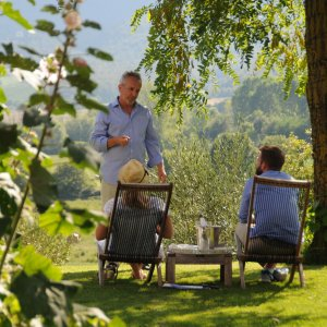 Malvin Tyler of Siena House in the country house garden he is wearing blue and standing before two people seated in deckchairs and welcoming a honeymoon couple with a glass of fizz and a little guidance on places we love.