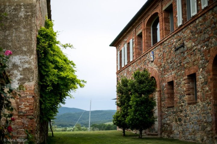 Image of a tuscan brick and stone hill top farm house built in the leopoldina style showing the smokehouse to the left and in the back ground the view of colle senese sienese hills