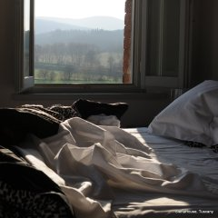 Image of unmade bed in a window with a glorious view and golden afternoon light in Tuscany