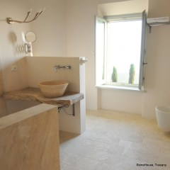Image of a large comfortable bathroom with heated stone flooring in white and shower clad in white stone Cypress trees visible from the open window