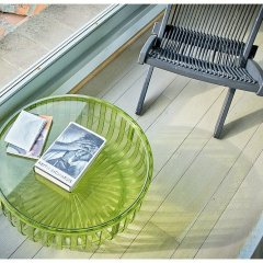 Image showing a starke coffee table and a black deck chair on a wooden surface in the storm gallery internal viewing platorm of a luxurious tuscan villa in siena with the keith richards autobiography sitting on the table