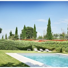 image showing the large pool in tuscan garden rosemary and cypress trees and white sun loungers photo by Rene Rickli