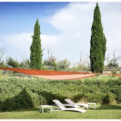 poolside image showing a tuscan garden lawn area with pair of pool loungers in white set against a rosemary covered slope under the shade of red shade sails cypress trees and blue sky