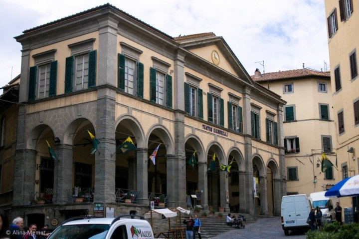 image showing a theatre front with a loggia for a covered market at ground level. the theatre is plastered and painted in yellow ochre with deep green external blinds and stone details there is some activity in the piazza and a few white vehicles are visible