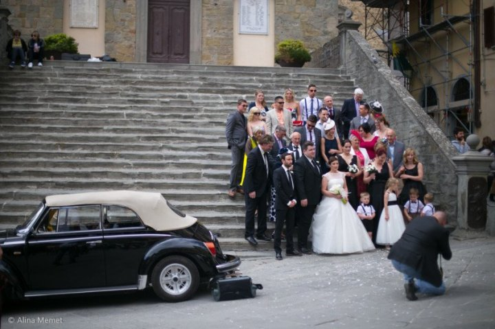 Image showing a wedding party being photographed in a tuscan hill town. They are standing on worn grey stone steps, with a convertible classic vw beetle in the foreground and the photographer of the wedding party is on one knee close to the car.