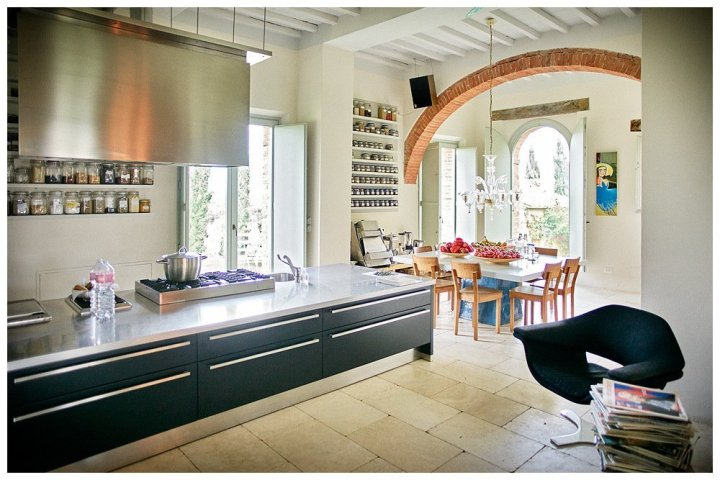 image showing a white interior in an old tuscan farmhouse with red brick arches and black and steel kitchen white stone floors designer furniture and art this is siena house boutique hotel in tuscany