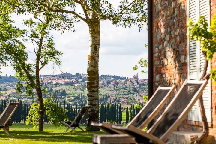 Image showing a summer garden scene at a tuscan country house two lounge chairs close to a wall in siena red red bricks and stone bright green grass lit by the setting sun and a hilltown visible from the garden in the background with cypresses and olive trees