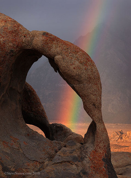 A view through an arch in the Alabama HIlls displays a rainbow against rainy skies.