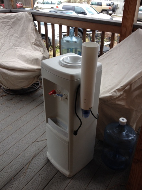 Water dispenser and bottles waiting to be returned to vendor.