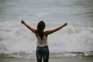 teen girl in white tank top and jeans standing in front of ocean