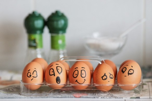 Dozen brown eggs with faces drawn on them