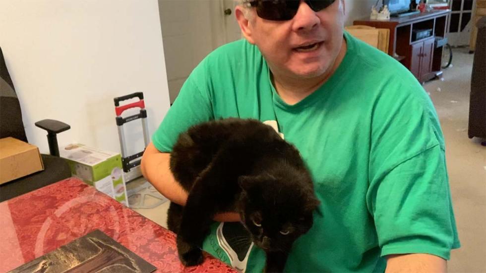 Joe holding his black cat, Midnight