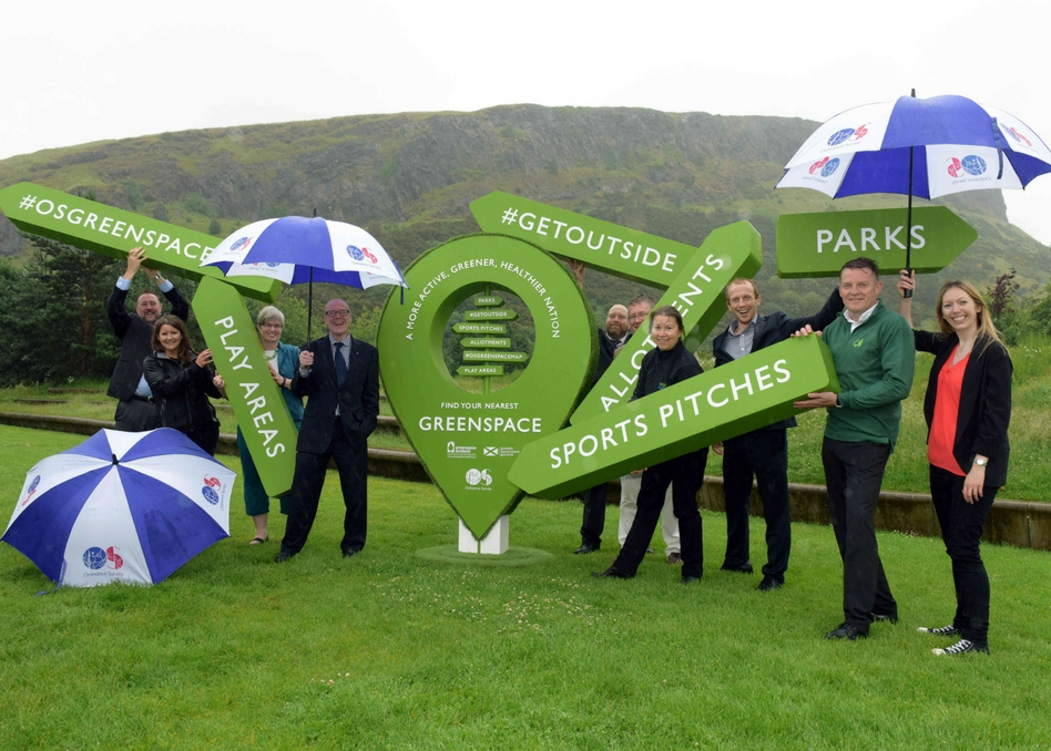 Greenspace signage with team on a hill