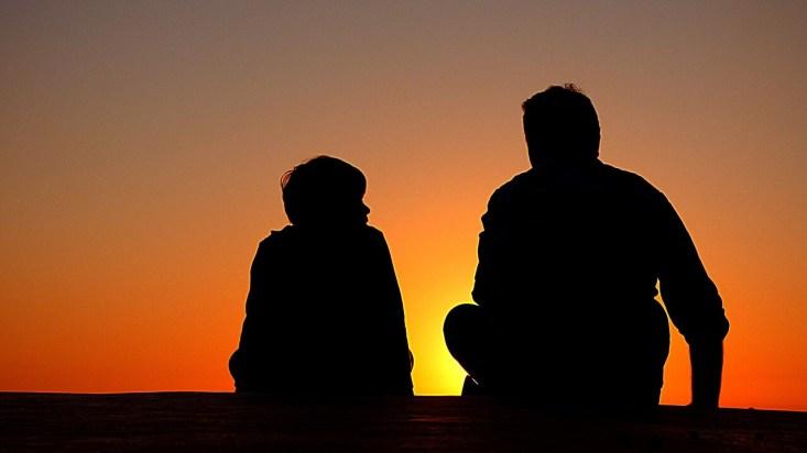 silhueta de pai e filho olhando o por do sol