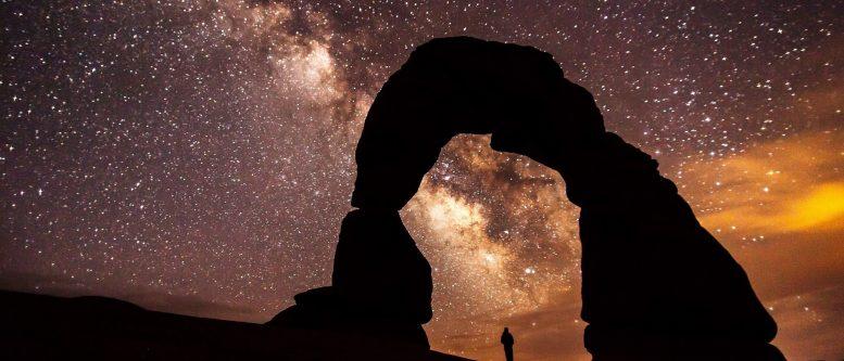 tourist-under-rocky-arch-at-night