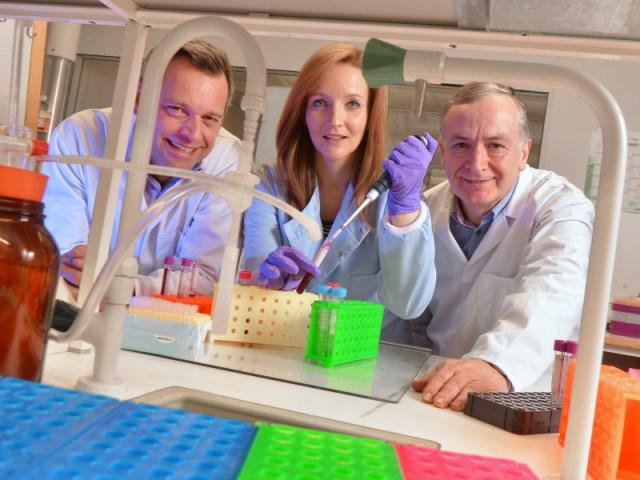 Une femme et deux hommes dans un laboratoire scientifique vêtus de blouses blanches.
