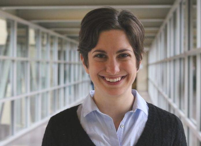 Femme aux cheveux noirs courts, vêtue d'une chemise bleu pâle et d'un pull noir, souriant dans un couloir.