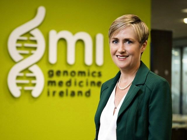 Dr Anne Jones dans un blazer vert foncé devant le signe de fond vert et blanc de GMI.