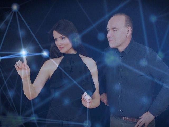 femme aux cheveux noirs et haut de dos nu noir à côté de l'homme en chemise bleue, traçant des lignes sur un écran futuriste.