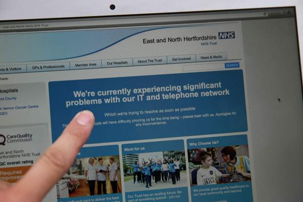 In this posed picture photograph, a woman points to the website of the NHS: East and North Hertfordshire notifying users of a problem in its network, in London on May 12, 2017. Several British hospitals were hit by cyber attacks on Friday, the country's health service said, forcing some to divert ambulances to other clinics and urge people not to try to contact their doctors. / AFP PHOTO / Daniel LEAL-OLIVASDANIEL LEAL-OLIVAS/AFP/Getty Images