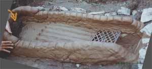 6. Bau der Feuerkammer: Ein Erdballen stützt das spätere Abzugsloch. Das Tretbrett einer alten Pfaff- Nähmaschine dient als Feuerrost.