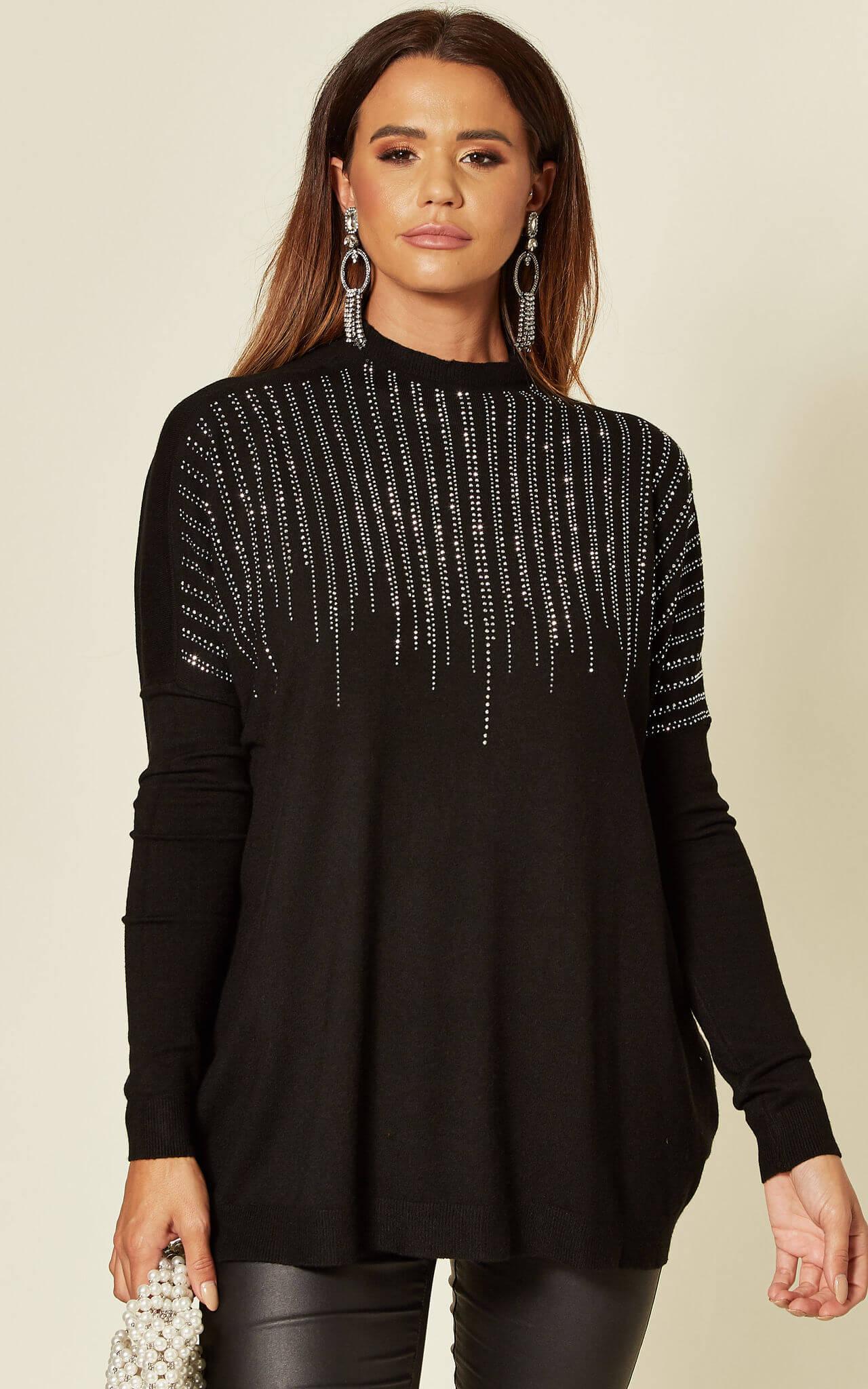 Model wears a black embellished jumper with black jeans