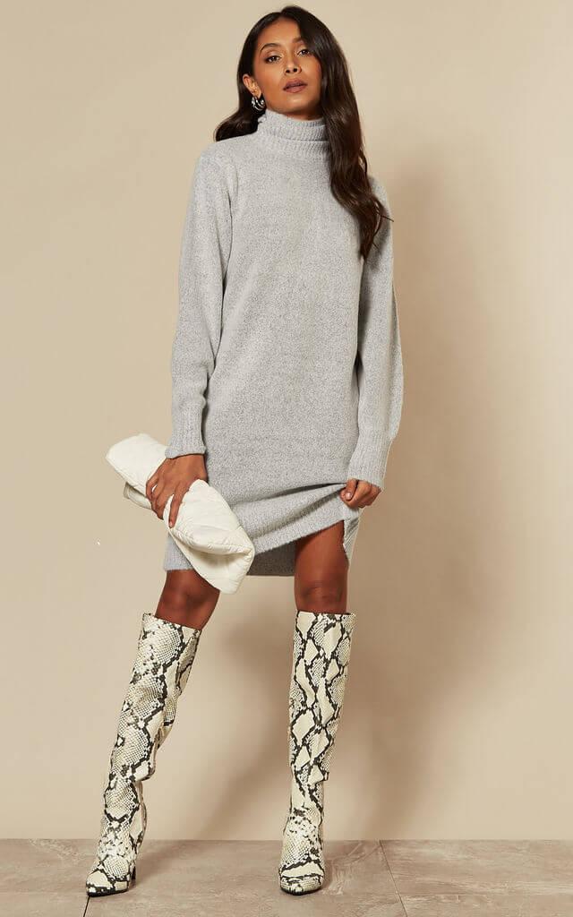Model wears high neck light grey jumper dress with knee high snake print boots