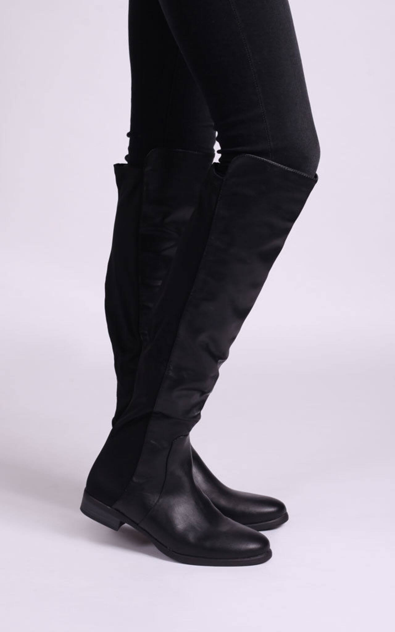 Model wears flat soled round toes boots over jeans