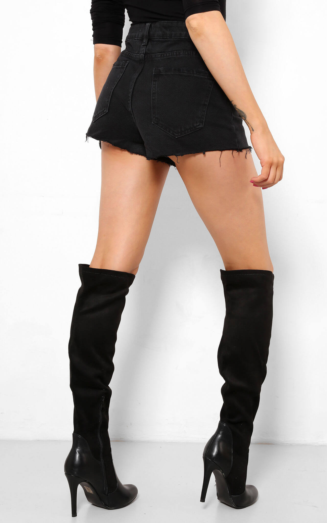 Model wears black suedette over the knee boots with stiletto heel
