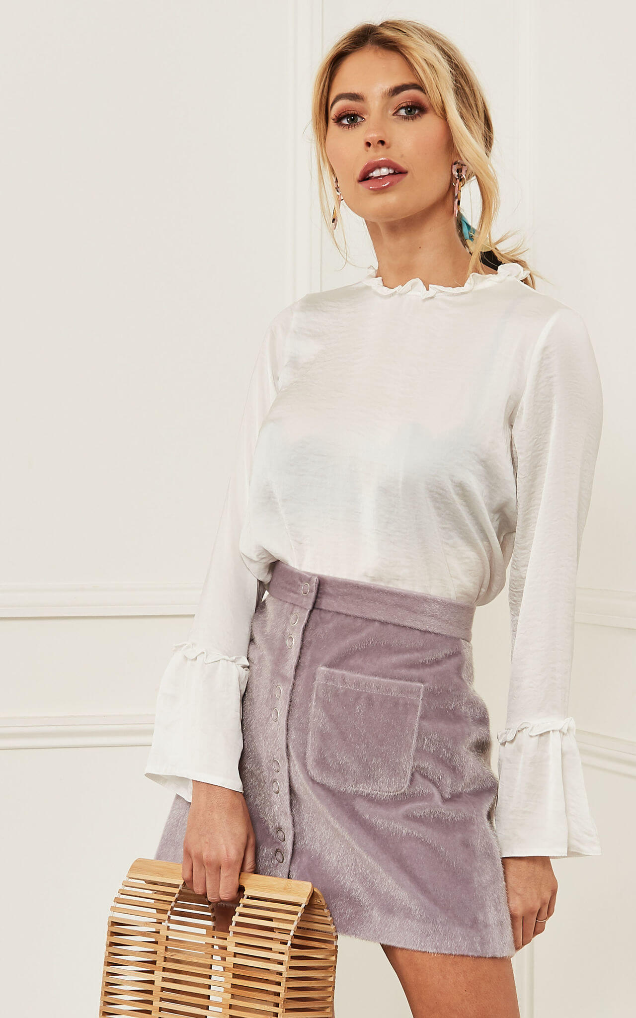 Model wears white frill neck blouse with purple skirt