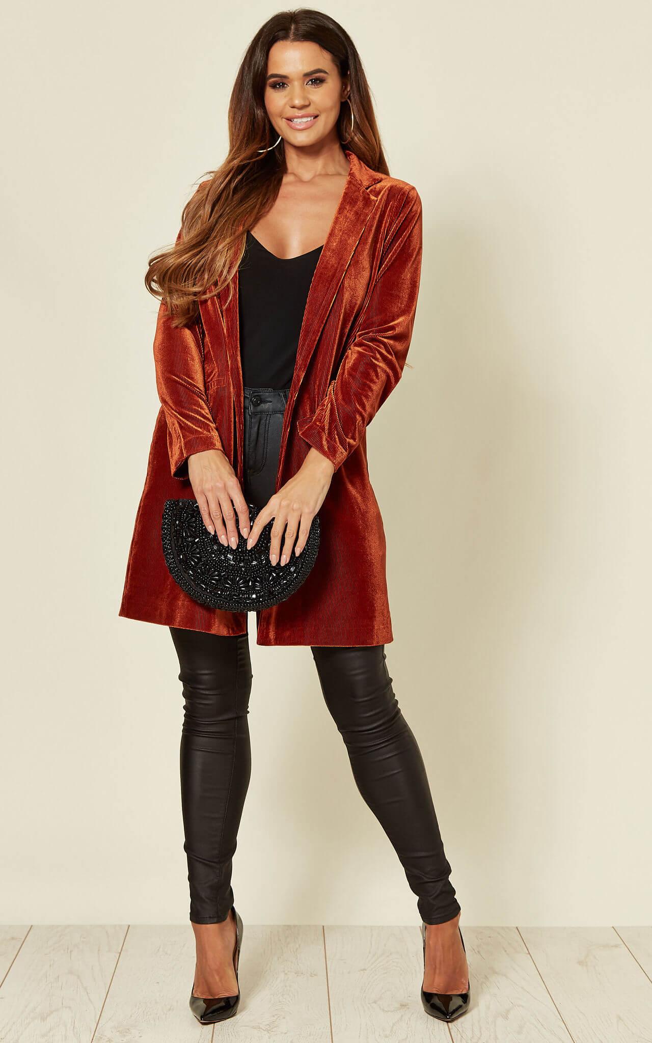 Model wears black jeans ad a rust coloured velvet blazer