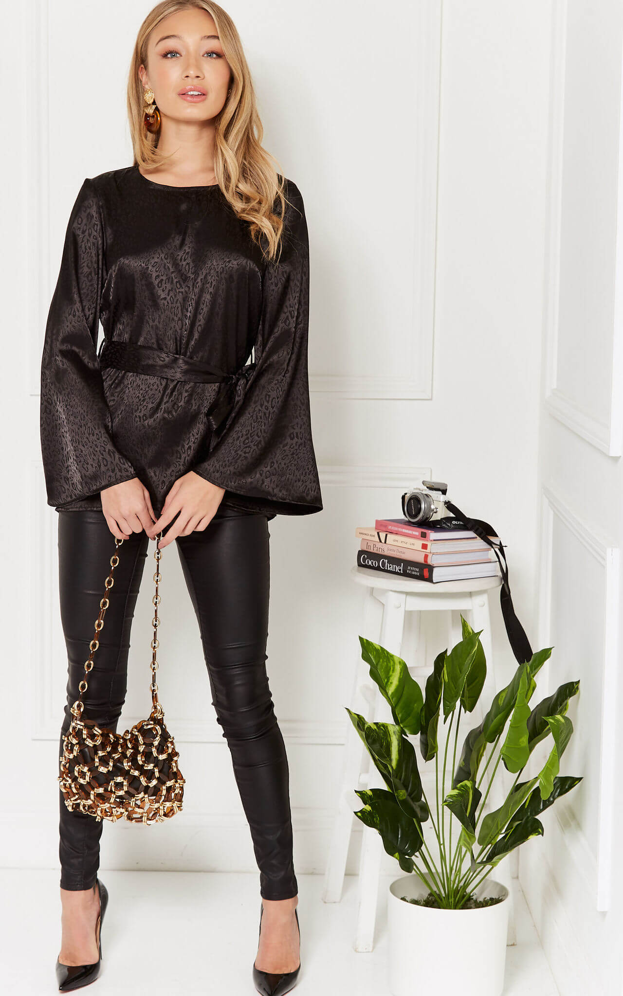 Model wears a black jacquard leopard print blouse with black jeans next to a plant and table with stacked books