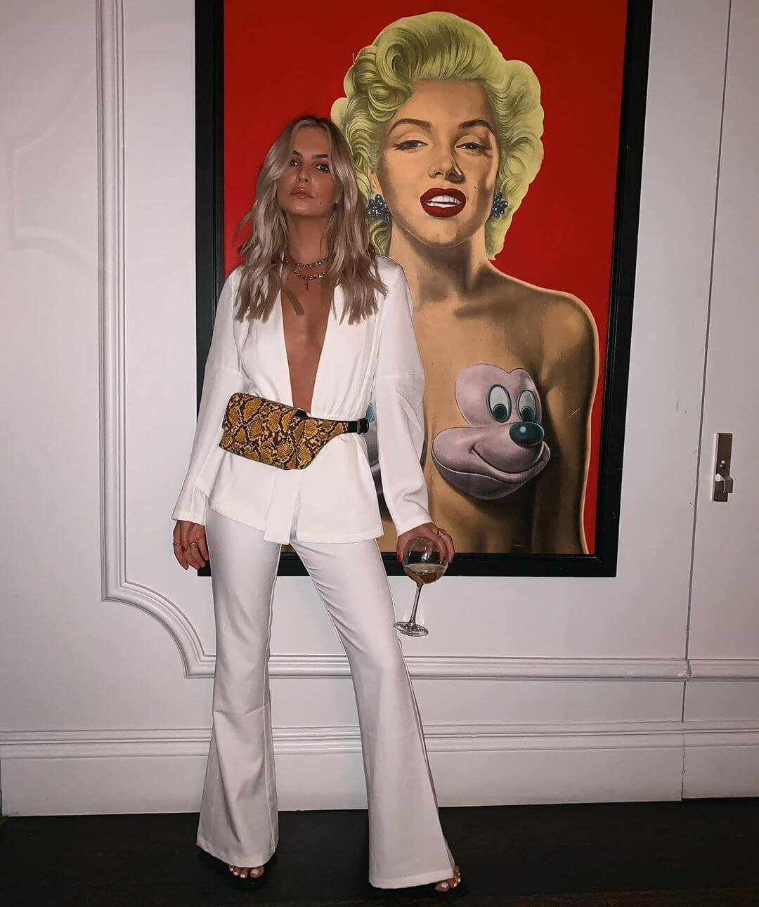 London influencer in front of painting wears white morgan blazer and trouser set