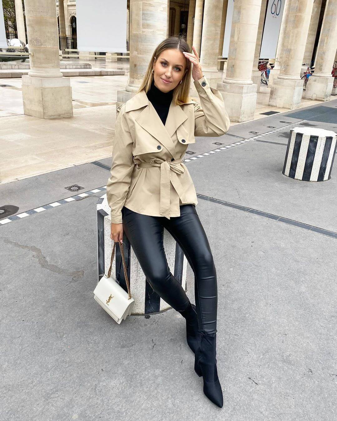 London influencer sits on bollard while wearing jacket and coated black jeans