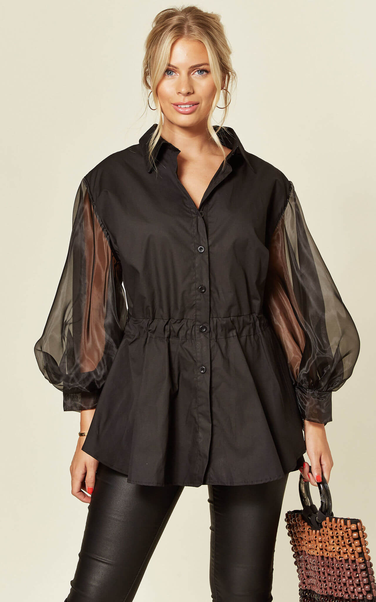 Model wears shirt in black with peplum and organza long sleeves