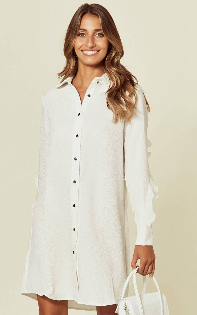 Model wears white shirt dress with long sleeves