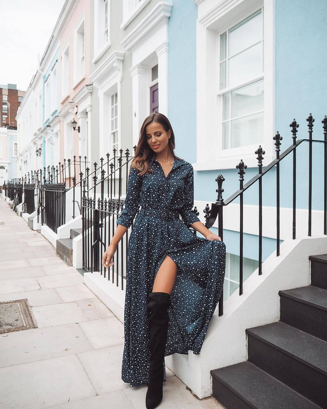 London influencer wears dove maxi dress in front of a row of colourful houses